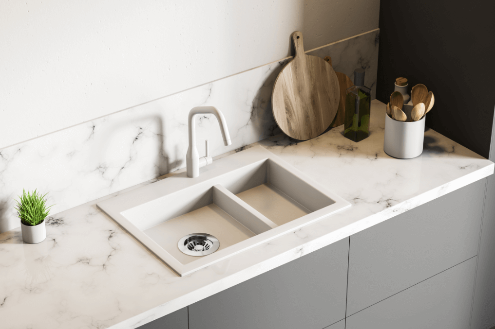 kitchen sink with plant, chopping board and pot of utensils